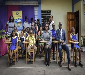 State Minister in the Ministry of National Security Senator Pearnel Charles Jr. and Commissioner of Corrections Ms. Ina Hunter join the students of St. Michael's Primary School in testing out the brand-new combination desks and chairs.
