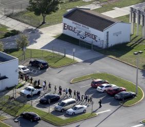 Students are evacuated by police from Marjory Stoneman Douglas High School in Parkland, Fla., on Wednesday, Feb. 14, 2018, after a shooter opened fire on the campus.