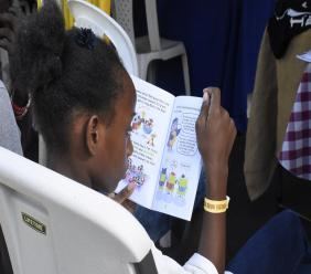 A young girl reads privately at the 2018 staging of Kingston Book Fair in March.