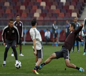 Mexico's Andres Guardado, center, and Mexico's Rafael Marquez, right, compete for the ball during Mexico's official training on the eve of the group F match between Germany and Mexico at the 2018 football World Cup in the Luzhniki Stadium in Moscow, Russia, Saturday, June 16, 2018. (AP Photo/Eduardo Verdugo).