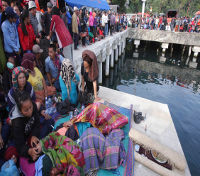 Relatives of victims of a sunken ferry wait for news at the Tigaras port in Toba lake, North Sumatra, Wednesday, June, 20, 2018. Officials said that over a hundred people are still missing from a ferry sinking early this week at a popular lake in Sumatra as distraught and angry relatives pleaded Wednesday for a bigger search effort. (AP Photo/Binsar Bakkara)