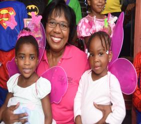 "Denise Samuels, HR and Training manager, JPPC flashes a megawatt smile as she snuggles these two angels from the Bower Bank Basic school during a Child's Day visit to the school. The school, which twinned the day with costume-day was one of four recipients of toys, supplies and smiles to children from East Kingston community as part of the company's annual ""Happy Faces"" programme."