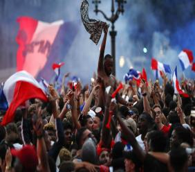 People react outside the Paris town hall after France defeated Belgium in the World Cup semifinal match between France and Belgium, Tuesday, July 10, 2018 in Paris. France advanced to the World Cup final for the first time since 2006 with a 1-0 win over Belgium on Tuesday. (AP Photo/Jean-Francois Badias)