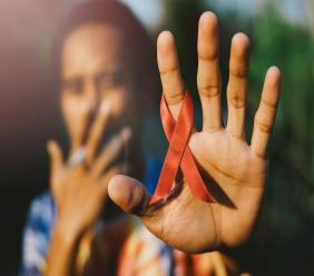 Stock image of a man with a red AIDS ribbon in hand. (PHOTO: iStock)