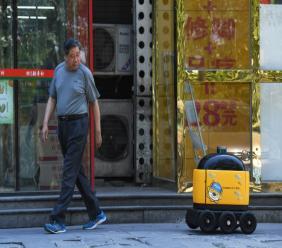 Une femme récupère ses provisions acheminées par un robot livreur au cours d'une démonstration à Pékin, le 28 juin 2018