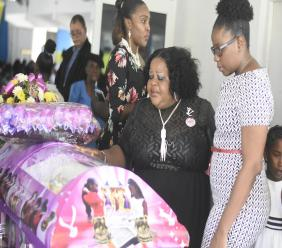 Mourners view the casket bearing the remains of 14-year-old Yetanya Francis, who was raped and murdered near her home in Arnett Gardens, St Andrew on August 23.