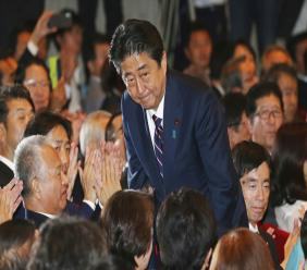 Liberal Democratic Party President Shinzo Abe bows as he receives applause from the LDP lawmakers shortly after his name was called as the winner of the ruling party presidential elections at its headquarters in Tokyo, Thursday, Sept. 20, 2018. (AP Photo/Koji Sasahara)