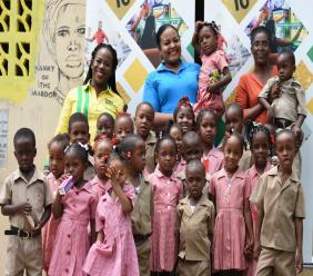 Supreme Ventures Limited (SVL) Corporate Communications Officer, Stephanie Todd (left), Ayesha Allen of the Gift of Love Foundation and Collette Nevers, Principal of the Nine Turns Basic School take a photo with students.