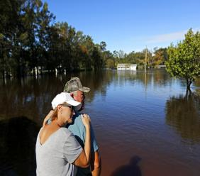 "Dianna Wood, embraces her husband Lynn, as they look out over their flooded property as the Little River continues to rise in the aftermath of Hurricane Florence in Linden, N.C., Tuesday, Sept. 18, 2018. ""I'm still hopeful,"" said Lynn about his home which currently has water up to the front step. ""In another foot, I'll be heartbroken,"" he added. (AP Photo/David Goldman)"