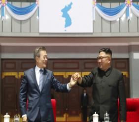 "South Korean President Moon Jae-in and North Korean leader Kim Jong Un hold their hands together after watching the mass games performance of ""The Glorious Country"" at May Day Stadium in Pyongyang, North Korea, Wednesday, Sept. 19, 2018. (Pyongyang Press Corps Pool via AP)"