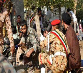 Iranian armed forces members and civilians take shelter in a shooting during a military parade marking the 38th anniversary of Iraq's 1980 invasion of Iran, in the southwestern city of Ahvaz, Iran, Saturday, Sept. 22, 2018. (AP Photo/ISNA, Behrad Ghasemi)