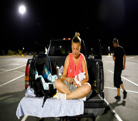 In this Monday, Oct. 15, 2018 file photo, Lorrainda Smith sits with her 2-day-old son, Luke, as she contemplates with her husband, Wilmer Capps, right, sleeping in their truck in a parking lot after their home was damaged from Hurricane Michael and they were told a nearby shelter was closed, in Panama City, Fla. (AP Photo/David Goldman, File)