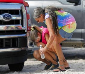 Nancy Register weeps as she is comforted by Roxie Cline, right, after she lost her home and all the contents inside to Hurricane Michael in Mexico Beach, Fla., Wednesday, Oct. 17, 2018.  (AP Photo/Gerald Herbert)
