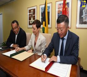 Health Minister, Dr Christopher Tufton (left), observes as Foreign Affairs and Foreign Trade Minister, Senator Kamina Johnson Smith (centre), and Chinese Ambassador to Jamaica, Tian Qi, sign an Economic and Technical Co-operation Agreement to facilitate the provision of approximately US$36.16 million in grant support from the Chinese Government to construct the Western Children's Hospital in Montego Bay, St. James.