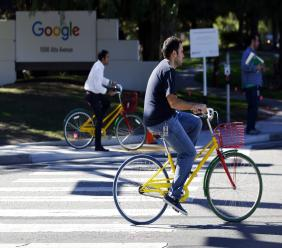 Employees ride company bicycles outside Google headquarters in Mountain View, California. (AP Photo/Marcio Jose Sanchez, File)