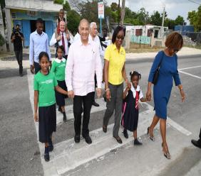 Students at Hazard Primary School are escorted across the pedestrian crossing by Parris Lyew-Ayee (second left), chairman of the JN Foundation; Rose Miller (third left), grants manager, JN Foundation; Mary Smith, Board Member of the JN Foundation and Mike Henry (in the background), Minister without Portfolio in the Office of the Prime Minister and Member of Parliament for the constituency.