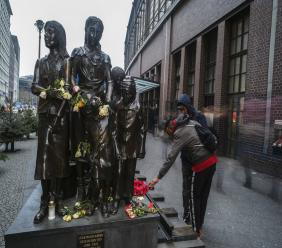 People pass a commemorative memorial statue to perpetuating the memory of the 'Kindertransport' (children transport) near Friedrichstrasse train station in central in Berlin, Germany, Monday, Dec. 17, 2018. (AP Photo/Markus Schreiber)