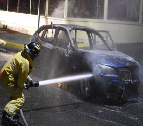 A firefighter extinguishing the blaze that engulfed an X1 motorcar on busy Hope Road in St Andrew on Tuesday evening. (Photos: Marlon Reid)