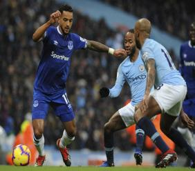 Manchester City's Fabian Delph, right, and  Raheem Sterling, centre challenge Everton's Theo Walcott, left, during their English Premier League football match  at Etihad stadium in Manchester, England, Saturday, Dec. 15, 2018.