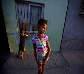 """In this Dec. 10, 2018 photo, Solgreidy, 8, and her 3-year-old brother Elvis stand outside of their uncle's home in Punto Fijo, Venezuela. """"I told her goodbye,"""" Solgreidy said, crying. """"And since then I haven't seen her again."""" (AP Photo/Fernando Llano)"""