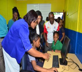 Students of Garden Hill Primary School, St. Catherine get help from their principal Shakira Hansel-Hudson (left) during the official handing over of 8 computers, a printer and furniture in their new computer lab by representatives of the Rotary Club of Kingston and Murabeni Caribbean Power.