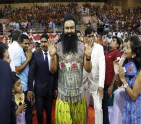 "FILE - In this Oct. 5, 2016 file photo, Indian spiritual guru who calls himself Dr. Saint Gurmeet Singh Ram Rahim Insan, center, greets followers as he arrives for a press conference ahead of the release of his new movie ""MSG: The Warrior Lion Heart,"" in New Delhi, India. (AP Photo/Tsering Topgyal, File)"