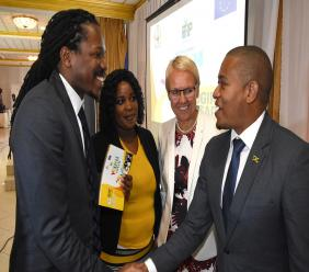 Minister of State in the Ministry of Education, Youth and Information the  Floyd Green (right) greets Senator Damion Crawford, opposition spokesperson on youth,  while Head of the European Union Delegation to Jamaica Ambassador Małgorzata Wasilewska (second right) and Desrine Bryce (centre), a beneficiary of the Poverty Reduction Programme look on.