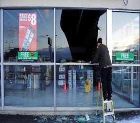 In this Nov. 30, 2018, file photo, Dennis Keeling, of Instant Services, measures for a broken window at an auto parts store following an earthquake in Anchorage, Alaska. (AP Photo/Mike Dinneen, file)