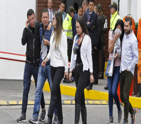 Family members of victims of a bombing gather outside the entrance to the General Santander police academy where the bombing took place in Bogota, Colombia, Thursday, Jan. 17, 2019. (AP Photo/John Wilson Vizcaino)