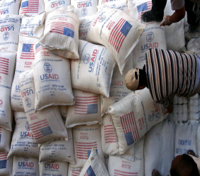 FILE - In this June 4, 2008 file photo, Palestinians unload bags of flour donated by the United States Agency for International Development, USAID, at a depot in the West Bank village of Anin near Jenin. (AP Photo/Mohammed Ballas, File)