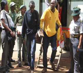 Pastor and activist Evan Mawarire, right, arrives handcuffed at the magistrates courts in Harare, Zimbabwe, Friday, Jan. 18, 2019. Zimbabwe Lawyers for Human Rights have said in a statement that Mawarire who is among the more than 600 people arrested this week has been charged with subverting a constitutional government amid a crackdown on protests against a dramatic fuel price increase.(AP Photo/Tsvangirayi Mukwazhi)