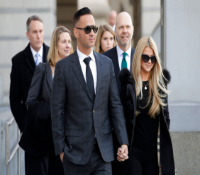 """FILE - IN this Jan. 19, 2018 file photo, Michael """"The Situation"""" Sorrentino, left, one of the former stars of the """"Jersey Shore"""" reality TV show, walks with his fiancee Lauren Pesce while leaving the Martin Luther King, Jr., Federal Courthouse after a hearing in Newark, N.J. (AP Photo/Julio Cortez, File)"""