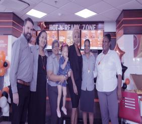 Patrice Roberts with Regional Manager Rafael Moraga and Brand Manager Michelle Borel, both on left as well as staff of Little Caesars.