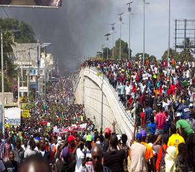 In this Feb. 7, 2019 photo, thousands of demonstrators march in the street as they chant anti-government slogans during a protest to demand the resignation of President Jovenel Moise and demanding to know how Petro Caribe funds have been used by the current and past administrations. (AP Photo)