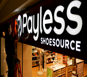FILE- In this May 18, 2006, file photo a worker puts the finishing touches on a sign unveiling the company's new look at a Payless Shoesource store at a mall in Independence, Mo. Payless ShoeSource has filed for Chapter 11 bankruptcy protection and is shuttering its remaining stores in North America. The filing on Monday, Feb. 18, 2019, came a day after the shoe chain began holding going-out-of-business sales at its North American stores. (AP Photo/Charlie Riedel, File)