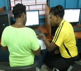 Social Development Commission (SDC), Capacity Development Coordinator, Parsha Allen (right), assists a young woman with résumé writing during an SDC training session.