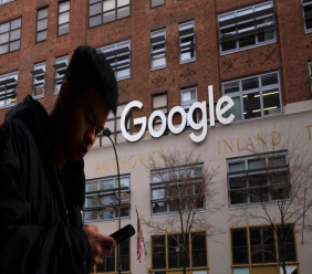 FILE - In this Dec. 17, 2018, file photo a man using a mobile phone walks past Google offices in New York. Google says it plans to launch a video-game streaming platform called Stadia, positioning itself to take on the traditional video-game business. (AP Photo/Mark Lennihan, File)