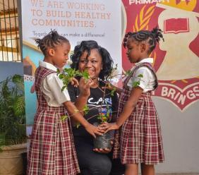 Sandals Foundation Ambassador Kadeen Black presents a cherry tree to Cleopatra Smith (left) and Amona Morris (right), grade one students of the John Rollins Success Primary School in St. James, last year.