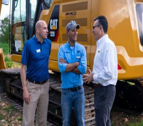 Angel Gomez (right), IMCA Jamaica's Country Director, stands alongside Caterpillar Inc.'s Todd Lange (left), Commercial Product Manager, and Carlos Chavez, Systems Application Specialist, in front of the new CAT 320 Next Generation Excavator at the launch of the company's two newest products.