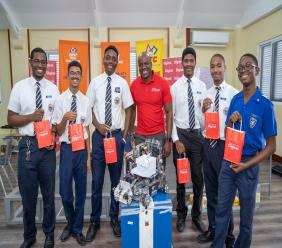 Posing with Public Relations and Communications Manager for Digicel (middle) and their robot are sixth form students Mickeil Phillipps, Marc Anthony Waton, David Smith (captain), Yohance Cockett, Rashaun Thompson and Joely Henry (third form).