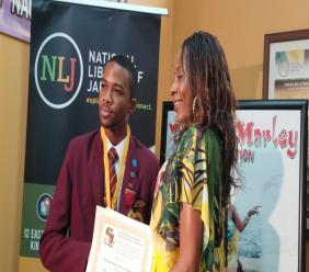 Wolmer's Boy's School student David Salmon, last year's winner of the Rita Marley Essay Competition, collects his certificate from Rosemary Duncan, manager of the Rita Marley Foundation.