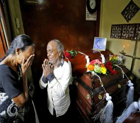 A Sri Lankan family mourns next to the coffins of their three family member, all victims of Easter Sunday bombing, in Colombo, Sri Lanka, Tuesday, April 23, 2019. (AP Photo/Eranga Jayawardena)