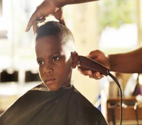 iStock photo of a little boy getting his head shaved by a barber.