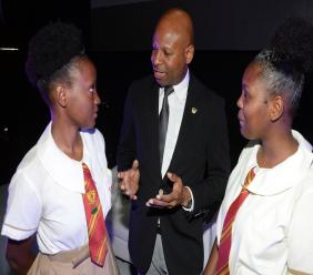 Michael Collins, Sales Development Specialist at JN Bank (centre), converses with students from Mona High School, during the Careers in International Fashion Symposium held at the Courtleigh Auditorium in New Kingston recently.