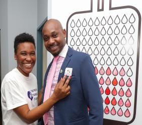 Sereka Sterling, Founder of the Preemie Foundation of Jamaica, gifts Otis Hamilton, Sagicor Life Financial Advisor, with a sticker thanking him for his donation of blood at a blood drive hosted by Sagicor Life.