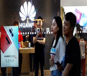 In this Monday, May 20, 2019, photo, shoppers visit a Huawei store in Beijing. Chinese tech giant Huawei has filed a motion in U.S. court challenging the constitutionality of a law that limits its sales of telecom equipment. (AP Photo/Ng Han Guan)