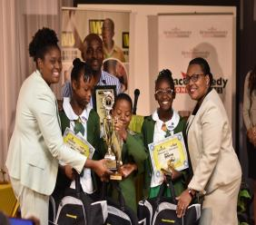 Mona Heights Primary are the champions of the 2019 Western Union IPLEDGE Primary Schools' Debate competition. Here, the winning team of Alissen Bowley, Aaden Dunn and Shallae Gavin, along with their coach Alex Hepburn pose with (from left) GraceKennedy Money Services (GKMS) Country Manager Jamaica Margaret Campbell and GKMS President and CEO, Grace Burnett.