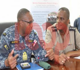 Commander of the Barbados Coast Guard, Lieutenant Commander Ryan Alleyne in discussion with the Deputy Commissioner of Police, Erwin Boyce