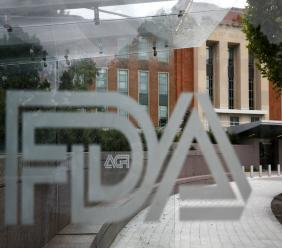 FILE - This Thursday, Aug. 2, 2018, file photo shows the U.S. Food and Drug Administration building behind FDA logos at a bus stop on the agency's campus in Silver Spring, Md. (AP Photo/Jacquelyn Martin, File)