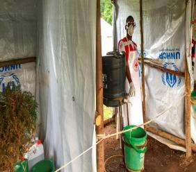 This photo taken Monday, June 10, 2019 and released by the International Rescue Committee (IRC), shows an Ebola screening checkpoint where people crossing from Congo go through foot and hand washing with a chlorine solution and have their temperature taken, at the Bunagana border crossing with Congo, in western Uganda. (Ben Wise/International Rescue Committee via AP)